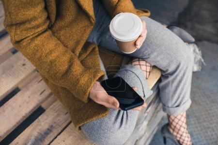 Photo for Partial view of stylish woman with coffee to go holding smartphone with blank screen - Royalty Free Image