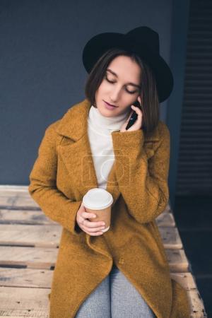 Photo pour Portrait de jeune femme à la mode avec café pour aller parler sur smartphone - image libre de droit