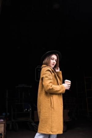 Photo pour Vue latérale d'une femme à la mode dans le chapeau et la veste maintenant café pour aller à la main - image libre de droit