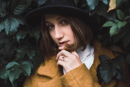 Beautiful woman among green leaves