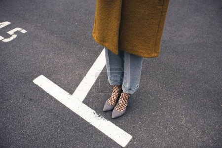 woman in stylish shoes standing on road