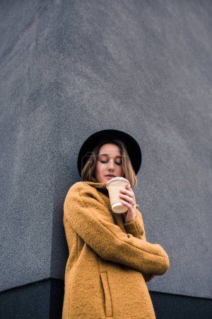 Photo for Portrait of beautiful young woman in hat with coffee to go in hand - Royalty Free Image