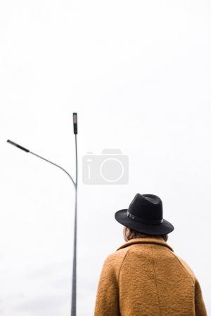 Photo for Back view of woman in black hat looking at street light - Royalty Free Image