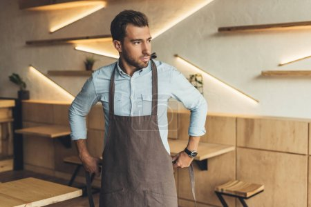 Photo for Portrait of worker looking away while wearing apron - Royalty Free Image