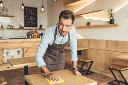 worker cleaning table in cafe