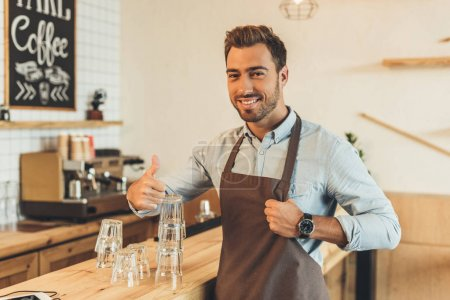 Photo for Portrait of barista showing thumb up while standing at counter - Royalty Free Image