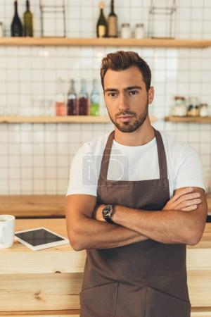Photo for Portrait of young barista in apron with arms crossed standing at counter in coffee shop - Royalty Free Image