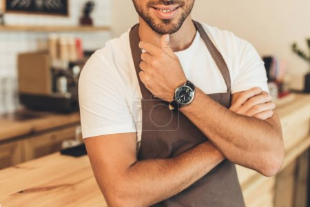Photo for Cropped shot of smiling barista in apron in coffee shop - Royalty Free Image