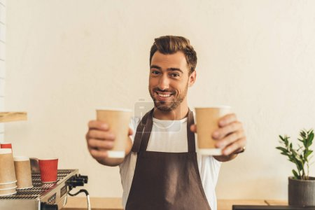Photo for Selective focus of smiling barista in apron showing coffee to go in hand sin coffee shop - Royalty Free Image