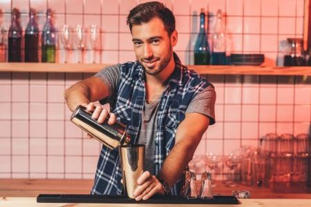 Photo for Portrait of smiling barman preparing alcohol cocktail at counter - Royalty Free Image