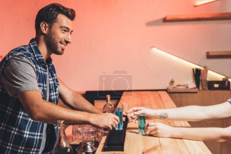 barman with alcohol shots on counter