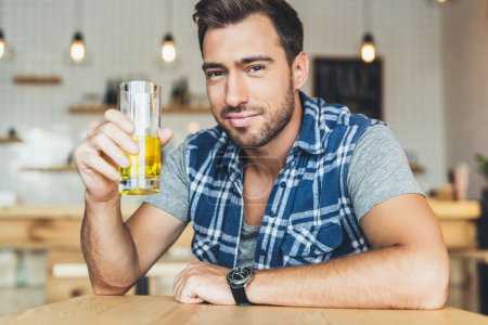 Photo for Portrait of man with glass of juice in hand looking at camera - Royalty Free Image