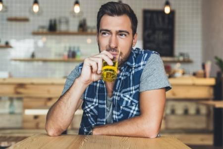 Photo for Portrait of young man drinking juice while sitting at table in cafe - Royalty Free Image