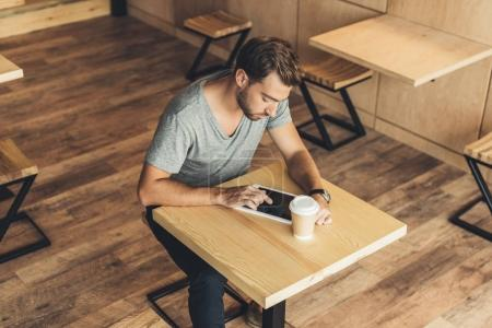 Photo for High angle view of concentrated man using tablet while spending time in cafe - Royalty Free Image