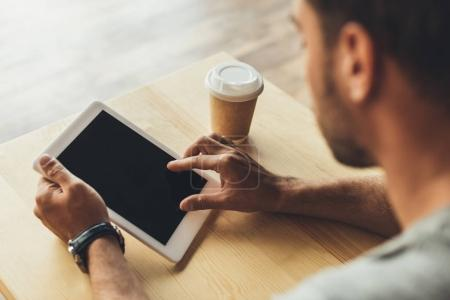 man using tablet in cafe