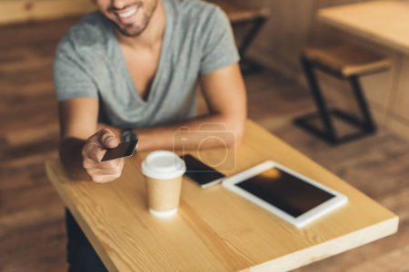 Man with credit card in cafe
