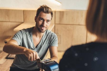 Photo pour Portrait d'un homme payant par carte de crédit dans un café - image libre de droit