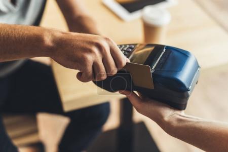 Photo pour Vue partielle de l'homme, payer pour commander par carte de crédit au café - image libre de droit