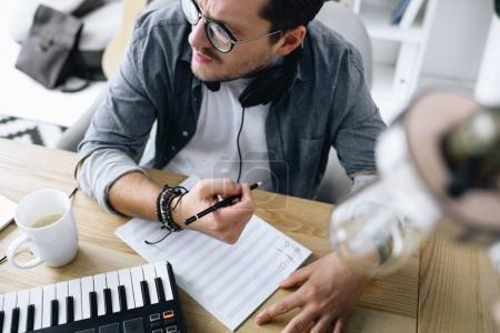 Photo pour Beau jeune compositeur, rédaction de notes sur lieu de travail - image libre de droit