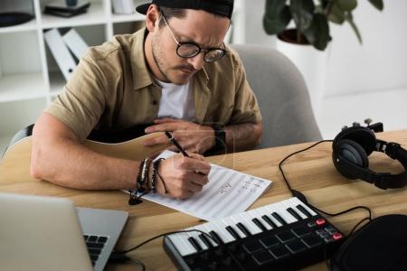 Photo pour Jeune musicien, rédaction de notes sur lieu de travail moderne - image libre de droit