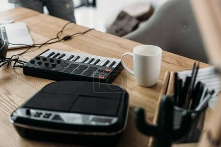 Foto de Vista cercana del lugar de trabajo del productor sano con pads de Mpc y taza de café - Imagen libre de derechos