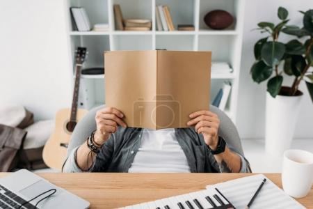 Photo for Musician reading magazine with blank cover at workplace - Royalty Free Image