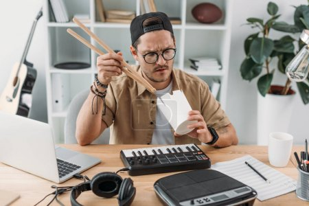 Musician eating chinese food with drumsticks