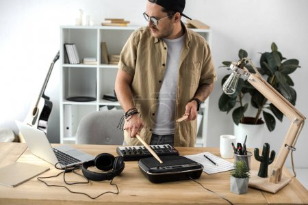 Photo for Handsome young musician playing on drum pad with sticks - Royalty Free Image