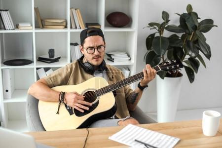 Photo pour Beau jeune homme jouant de la guitare et en regardant les notes - image libre de droit