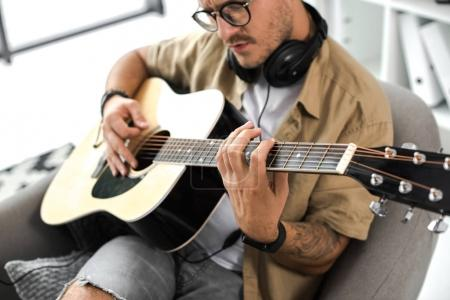 Photo for Focused stylish man playing acoustic guitar - Royalty Free Image