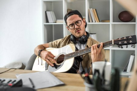 Photo for Focused young man playing acoustic guitar - Royalty Free Image