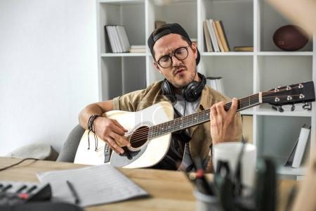 Photo pour Axé sur le jeune homme jouant de la guitare acoustique - image libre de droit