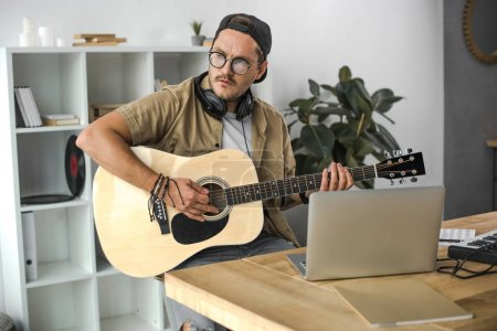 Photo for Focused stylish man playing acoustic guitar at workplace - Royalty Free Image