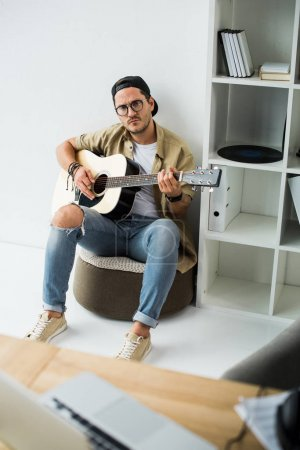 Photo for Focused stylish man playing acoustic guitar in office - Royalty Free Image