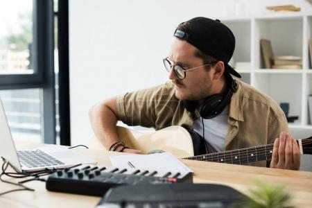 Photo for Musician playing guitar at workplace with MPC pad and laptop - Royalty Free Image