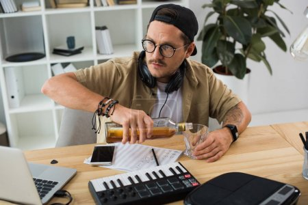 Musician pouring whiskey in glass