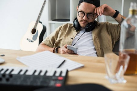 overworked musician using smartphone