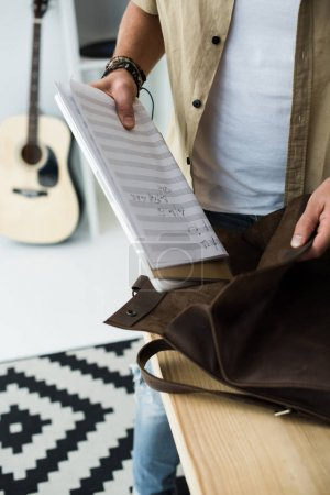 Photo for Cropped shot of musician putting music notebook into bag - Royalty Free Image