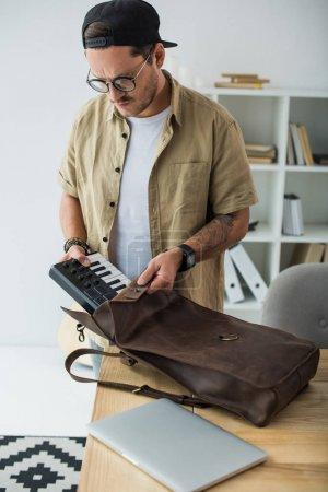 musician putting MPC pad into bag