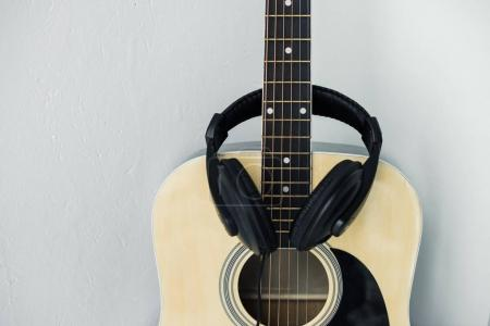 Photo for Minimalistic composition of acoustic guitar and headphones - Royalty Free Image