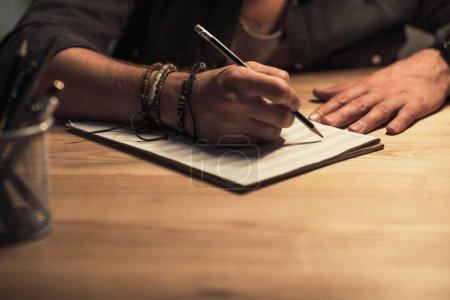 Photo pour Plan recadré d'un musicien écrivant dans un carnet de musique - image libre de droit