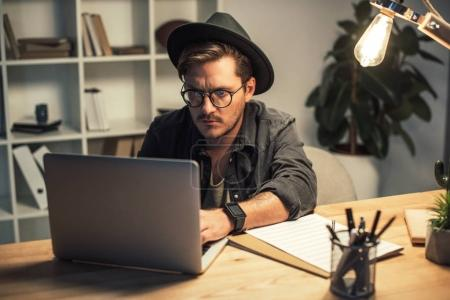 Photo for Young concentrated businessman using laptop in office at late night - Royalty Free Image