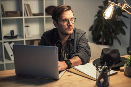 Photo for Young businessman using laptop in office at late night and looking away - Royalty Free Image