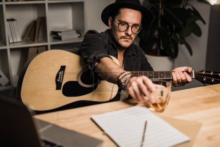 Photo for Young unsuccessful musician with acoustic guitar drinking whiskey at workplace - Royalty Free Image