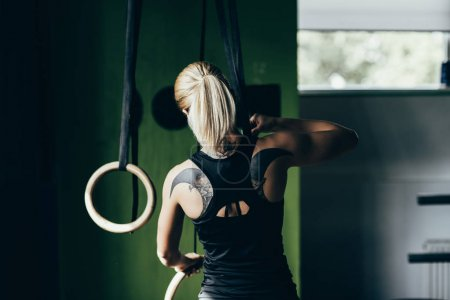 Sportswoman with gymnastic rings