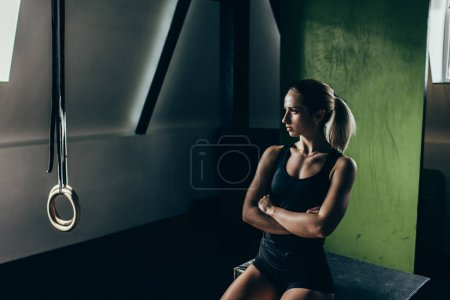 Athletic sportswoman posing with arms crossed