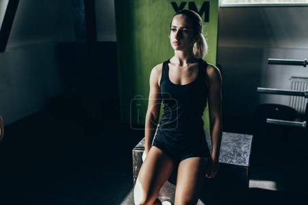 Photo for Young athletic sportswoman in sportswear sitting on a black wooden cube at gym - Royalty Free Image