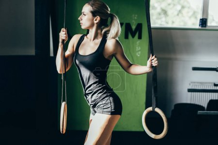 Sportswoman posing with gymnastic rings