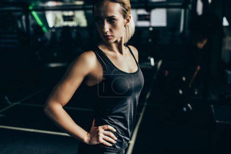 Athletic sportswoman with arms akimbo