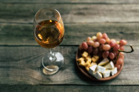Glass of white wine and grapes with cheese